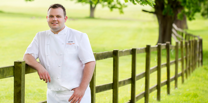 head chef from coworth park Berkshire poses next to a fence in the hotel grounds